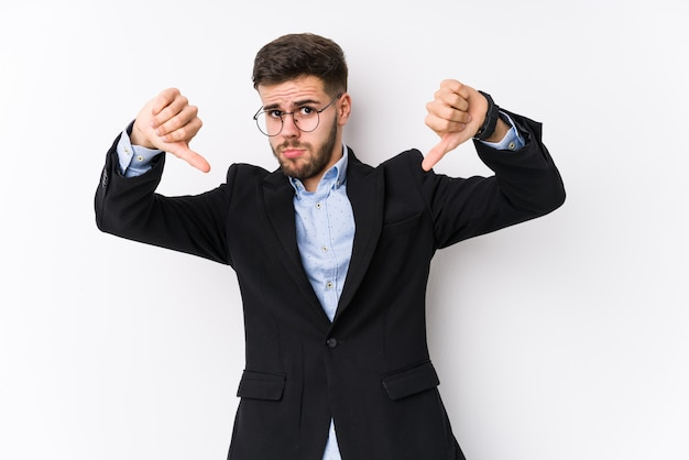 Young caucasian business man posing in a white wall isolated young caucasian business man showing thumb down and expressing dislike.