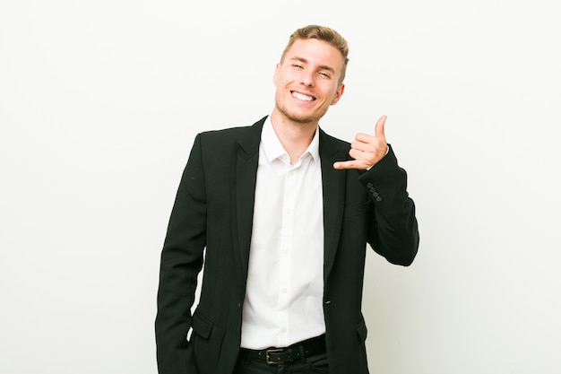 Young caucasian business man showing a mobile phone call gesture with fingers.