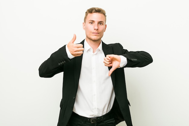 엄지 손가락을 보여주는 젊은 백인 비즈니스 남자와 아래로 엄지 손가락, 어려운 개념을 선택