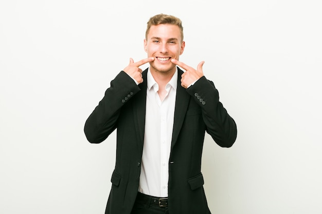Young caucasian business man smiles, pointing fingers at mouth.