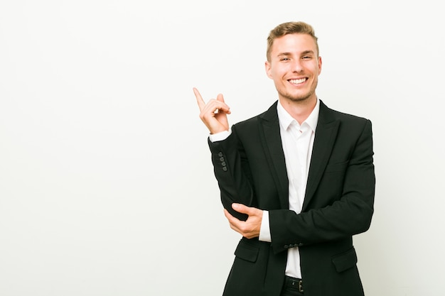 Young caucasian business man smiling cheerfully pointing with forefinger away.