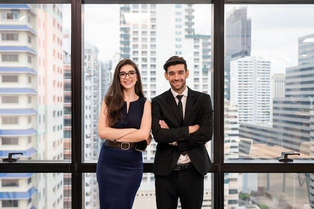 笑みを浮かべて、近代的なオフィスにカメラ目線で立っている若い白人ビジネスパートナー立って交差腕