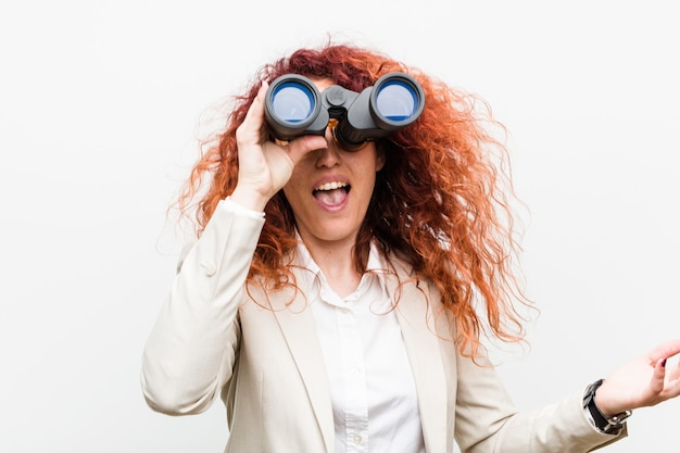 勝利または成功を祝う双眼鏡を保持している若い白人ビジネス赤毛の女性