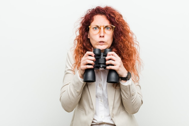 Young caucasian business redhead woman holding a binoculars biting fingernails, nervous and very anxious.