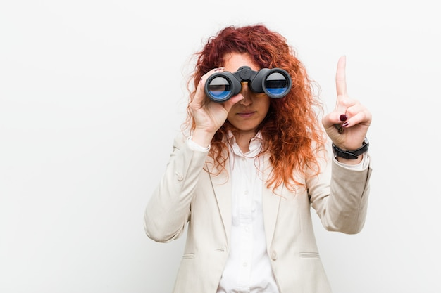 Young caucasian business redhead woman holding a binoculars showing number one with finger.