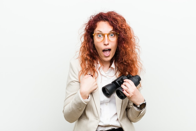 Young caucasian business redhead woman holding a binoculars surprised pointing at herself