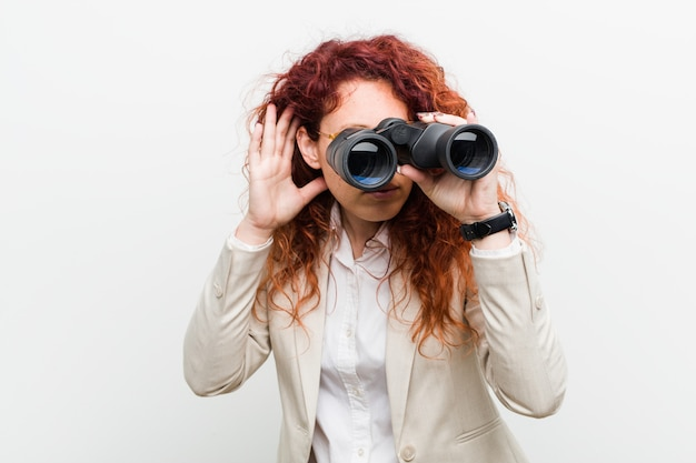 Young caucasian business redhead woman holding a binoculars trying to listening a gossip.