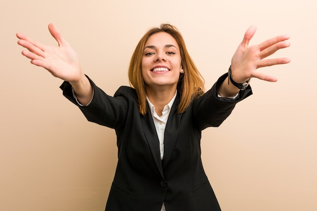 Young caucasian business woman feels confident giving a hug to the camera.