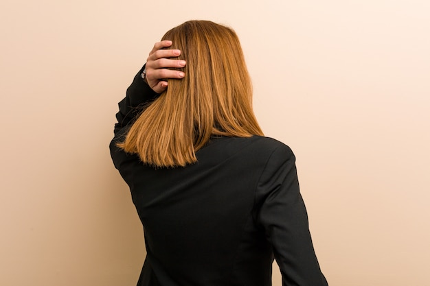 Young caucasian business woman from behind thinking about something.