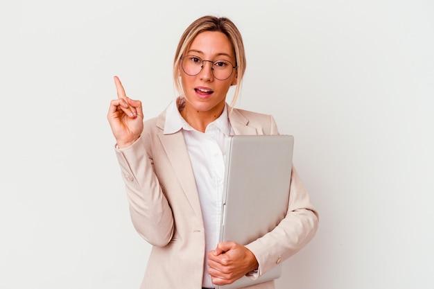 Молодая кавказская деловая женщина, держащая ноутбук, изолирована на белом, имея отличную идею, концепцию творчества.