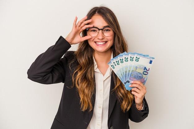 흰색 배경에 격리된 지폐를 들고 있는 백인 비즈니스 여성은 눈에 확인 제스처를 유지하는 데 흥분했습니다.