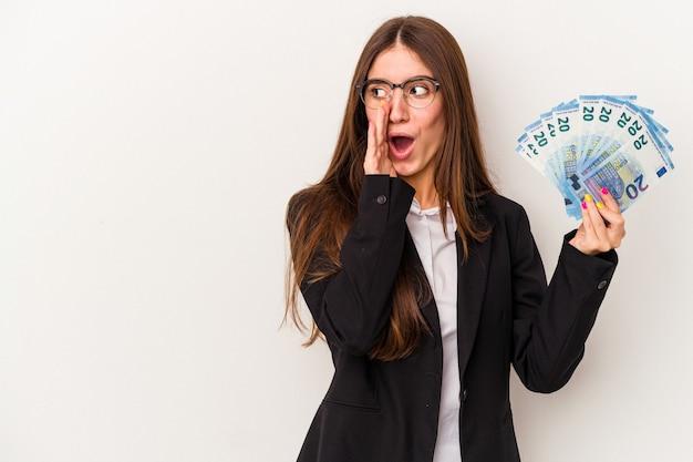 Молодая кавказская бизнес-леди, держащая банкноты, изолированные на белом фоне, говорит секретные горячие новости о торможении и смотрит в сторону