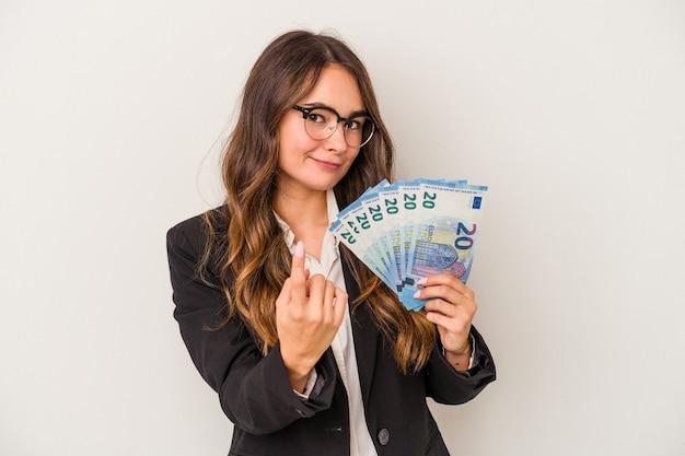 흰색 배경에 격리된 지폐를 들고 있는 젊은 백인 사업가가 마치 초대하는 것처럼 손가락으로 당신을 가리키고 있습니다.
