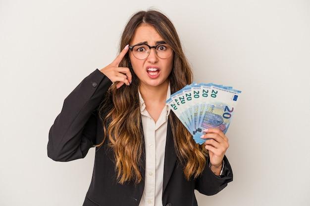 人差し指で失望のジェスチャーを示す白い背景で隔離の紙幣を保持している若い白人ビジネス女性。
