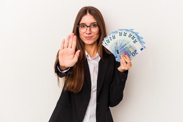 白い背景で隔離の紙幣を保持している若い白人のビジネス女性は、一時停止の標識を示している手を伸ばして立って、あなたを防ぎます。
