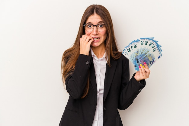 Young caucasian business woman holding banknotes isolated on white background biting fingernails, nervous and very anxious.