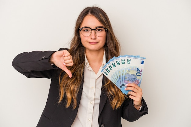 Young caucasian business woman holding banknotes isolated on white background showing a dislike gesture, thumbs down. disagreement concept.