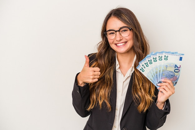 Young caucasian business woman holding banknotes isolated on white background smiling and raising thumb up