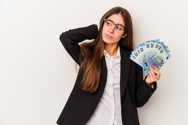 Young caucasian business woman holding banknotes isolated on white background touching back of head, thinking and making a choice.