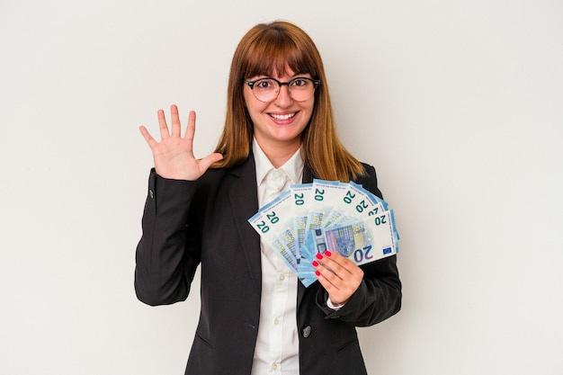Young caucasian business woman holding bills isolated on white background smiling cheerful showing number five with fingers.