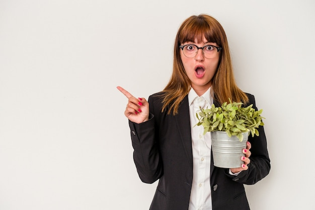 Young caucasian business woman holding a plant isolated on white background pointing to the side
