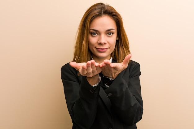 Young caucasian business woman holding something with palms, offering to camera.