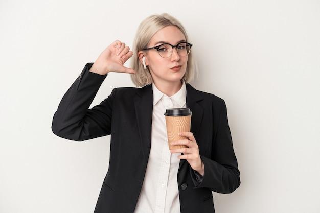 白い背景で隔離のテイクアウトコーヒーを保持している若い白人のビジネス女性は、誇りと自信を持って、次の例を感じます。