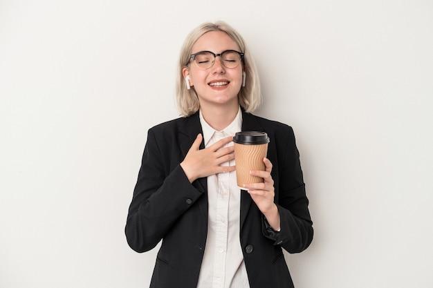 Молодая кавказская бизнес-леди, держащая кофе на вынос на белом фоне, громко смеется, держа руку на груди.