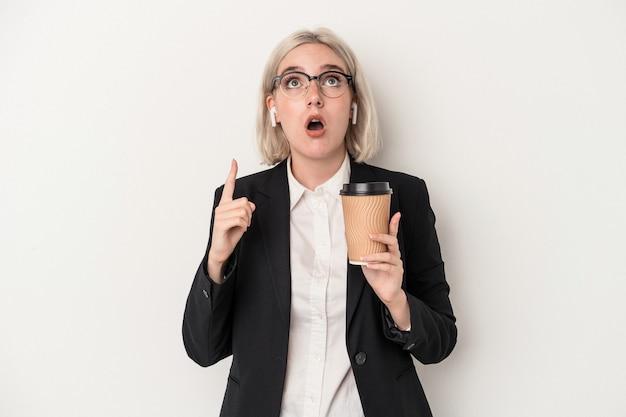 保持している若い白人ビジネス女性は、口を開けて逆さまを指している白い背景で隔離のコーヒーをテイクアウトします。