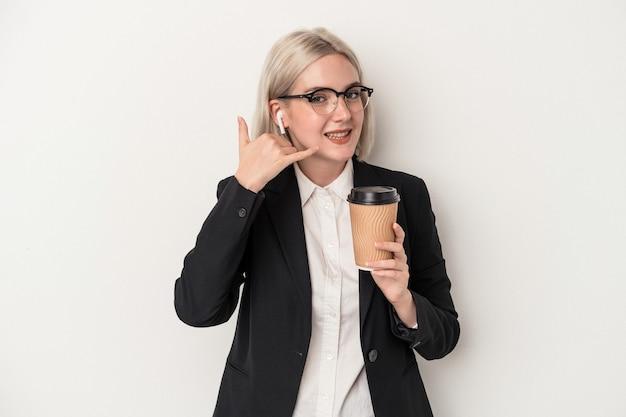 指で携帯電話の呼び出しジェスチャーを示す白い背景で隔離のコーヒーをテイクアウトを保持している若い白人ビジネス女性。