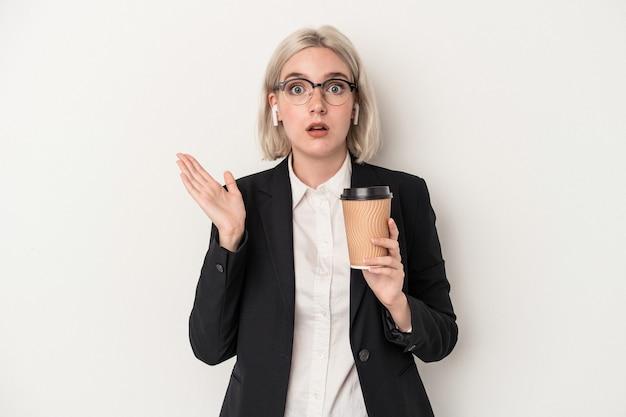 保持している若い白人ビジネス女性は、驚いてショックを受けた白い背景で隔離のコーヒーをテイクアウトします。