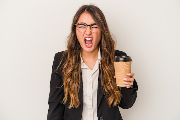Young caucasian business woman holding a takeaway coffee isolated on white background screaming very angry and aggressive.