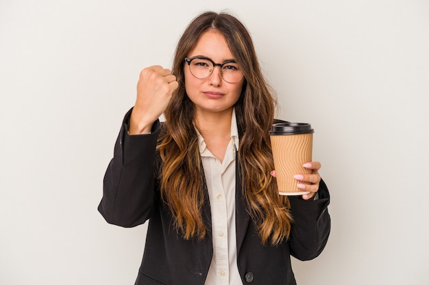 Young caucasian business woman holding a takeaway coffee isolated on white background showing fist to camera, aggressive facial expression.