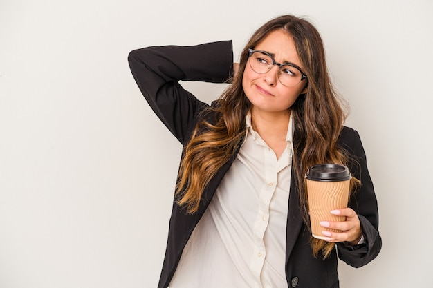 Young caucasian business woman holding a takeaway coffee isolated on white background touching back of head, thinking and making a choice.