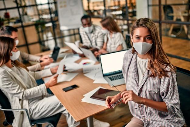 保護マスクを着用した若い白人ビジネスウーマンは、ラップトップに座って眼鏡を手に持ち、検疫条件下でオフィスでチームや同僚と協力しています。