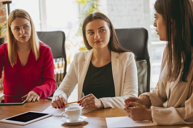 Молодая кавказская бизнес-леди в современном офисе с командой. творческая встреча, постановка задач. женщины во фронт-офисе работают. понятие финансов, бизнеса, женской силы, включения, разнообразия, феминизма.
