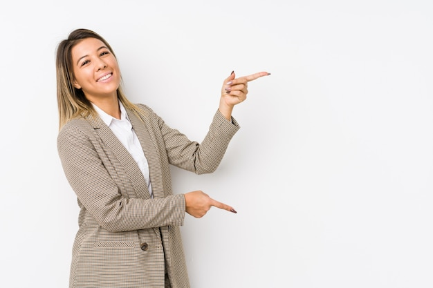 Young caucasian business woman isolated excited pointing with forefingers away.