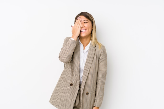 Young caucasian business woman isolated having fun covering half of face with palm.