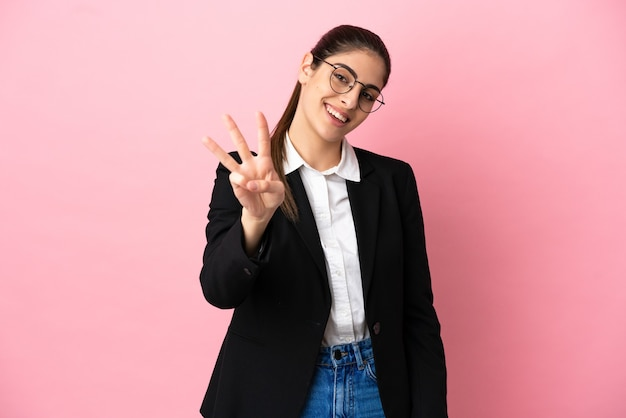 幸せなピンクの背景に分離された若い白人ビジネス女性と指で3を数える