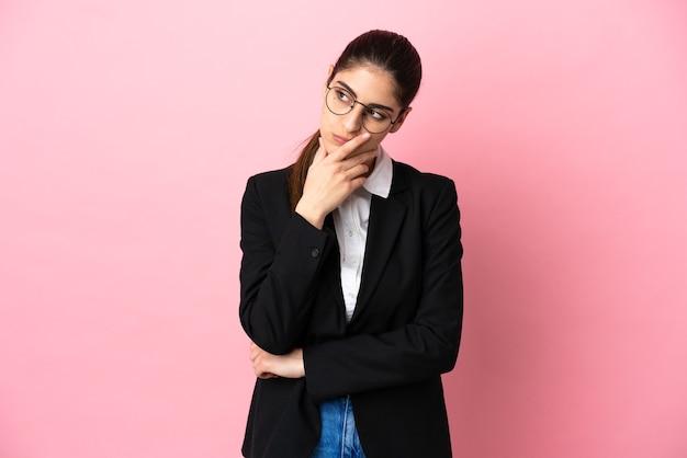 疑いを持って、混乱した表情でピンクの背景に分離された若い白人ビジネス女性