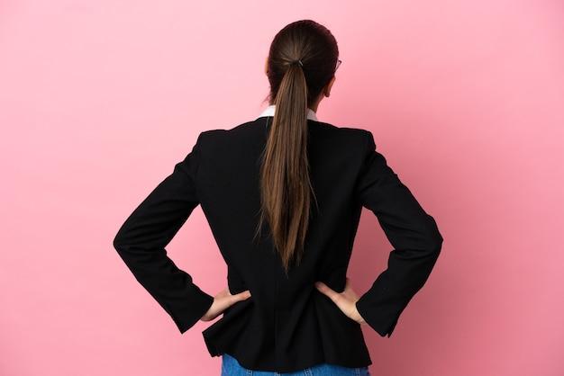 Молодая кавказская бизнес-леди изолирована на розовом фоне в задней позиции