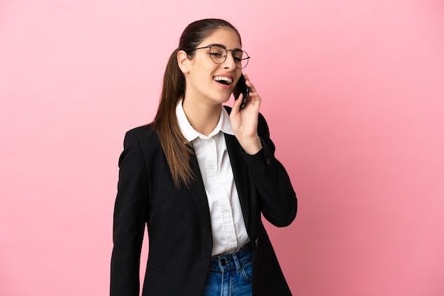 휴대 전화와 대화를 유지 하는 분홍색 배경에 고립 된 젊은 백인 비즈니스 여자