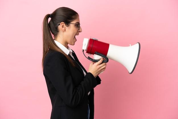 Молодая кавказская бизнес-леди, изолированная на розовом фоне, кричит в мегафон