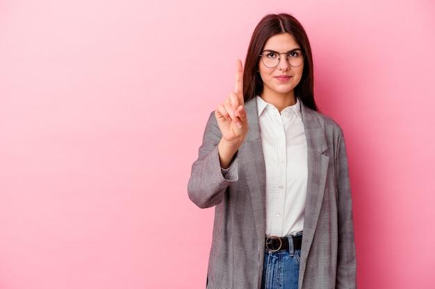 Молодая кавказская бизнес-леди, изолированные на розовом фоне, показывая номер один пальцем.