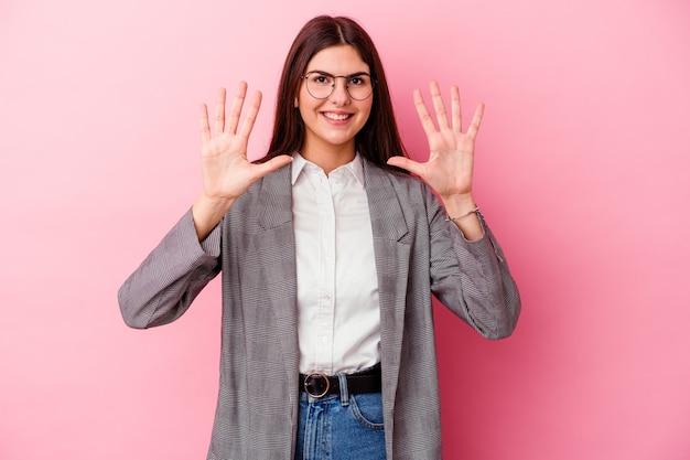 Молодая кавказская бизнес-леди изолирована на розовом фоне, показывая номер десять руками.