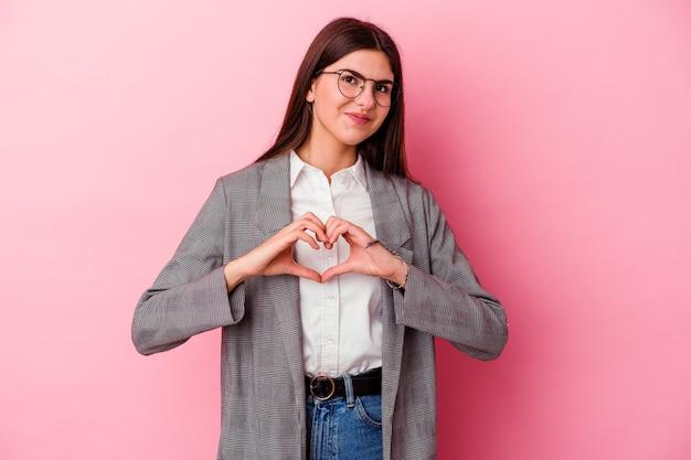 Молодой кавказский бизнес-леди, изолированных на розовом фоне улыбается и показывает форму сердца руками.