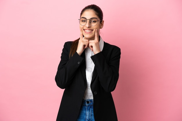 행복하고 즐거운 표정으로 웃는 분홍색 배경에 고립 된 젊은 백인 비즈니스 여자