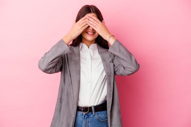 Молодая кавказская бизнес-леди, изолированная на розовой стене, закрывает глаза руками, широко улыбается, ожидая сюрприза.