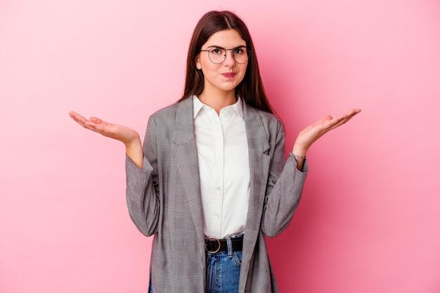 Молодая кавказская бизнес-леди изолирована на розовой стене, сомневаясь и пожимая плечами в вопросительном жесте
