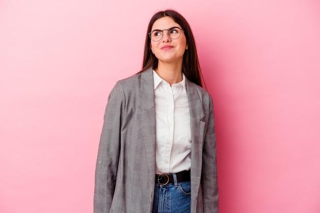 Молодая кавказская бизнес-леди изолирована на розовой стене, мечтающей о достижении целей и задач